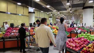UAE, DUBAI, FEBRUARY 1, 2016: People near shop counter with fresh fruits inside Dubai Mall in United Arab Emirates. Dubai Mall is the world largest shopping mall