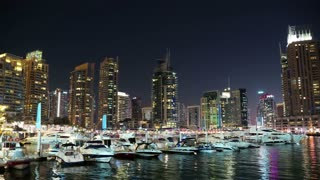 UAE, DUBAI, FEBRUARY 5, 2016: Dubai Marina night zoom in time lapse, United Arab Emirates. Dubai Marina - the largest man-made marina in the world. Dubai Marina is a canal city