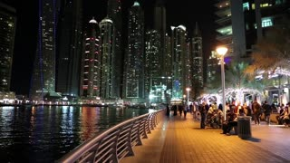 UAE, DUBAI, FEBRUARY 6, 2016: People on waterfront, night Dubai Marina, United Arab Emirates. Dubai Marina is a district in Dubai and largest man-made marina, artificial canal in the world