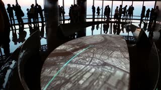 UAE, DUBAI, JANUARY 31, 2016: People near interactive map on observation deck on 125 floor inside Burj Khalifa megatall skyscraper in Dubai, United Arab Emirates
