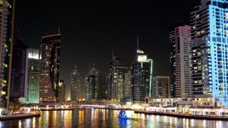 UHD 4K Dubai Marina night zoom out time lapse, United Arab Emirates. Dubai Marina - the largest man-made marina in the world, is a canal city, carved along a 3 km stretch of Persian Gulf shoreline