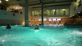 UKRAINE, BROVARY, NOVEMBER 25, 2013: People swim in blue pool inside water park.