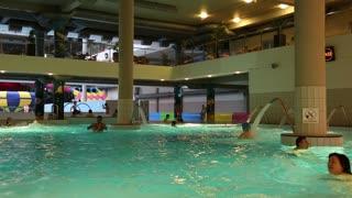 UKRAINE, BROVARY, NOVEMBER 25, 2013: People swim in blue pool inside water park