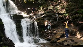UKRAINE, CARPATHIANS, AUGUST 4, 2014: People near beautiful waterfall in Carpathian Mountains, Ukraine. Shypit waterfall (English translation - Sizzle) is located on the Pylypets River