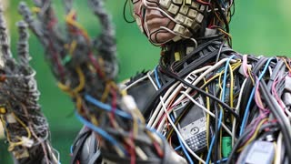 UKRAINE, KIEV, AUGUST 17, 2016: Sculpture of human, made of electric wires and electronic devices. Cyborg looks at his hands