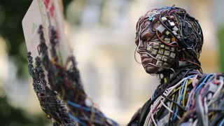 UKRAINE, KIEV, AUGUST 17, 2016: Sculpture of human, made of electric wires and electronic devices. Cyborg with book in hands. Robot reads a book