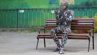 UKRAINE, KIEV, AUGUST 17, 2016: Sculpture of human, made of electric wires and electronic devices. Robot sits on the bench. Cyborg looks at his hands