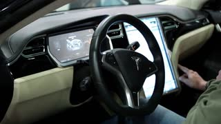 UKRAINE, KIEV, JUNE 10, 2016: Exhibition of electric cars. Man inside Tesla electromobile. Tesla electromobile interior
