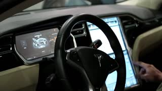 UKRAINE, KIEV, JUNE 10, 2016: People at exhibition of electric cars. Man inside Tesla electromobile