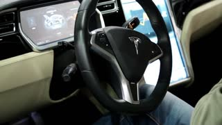 UKRAINE, KIEV, JUNE 10, 2016: People at exhibition of electric cars. Man with camera inside Tesla electromobile at exhibition of electric cars
