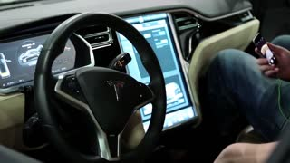 UKRAINE, KIEV, JUNE 10, 2016: People at exhibition of electric cars. Man with smartphone inside Tesla electromobile at exhibition of electric cars