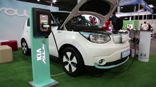 UKRAINE, KIEV, JUNE 10, 2016: People at exhibition of electric cars. White KIA Soul EV electromobile is being charged. Car with openned bonnet