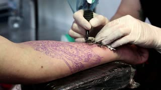 "UKRAINE, KIEV, MAY 10, 2013: People make a tattoos at the 9-th international tattoo festival ""Tattoo Collection 2013"" in Kiev, Ukraine"