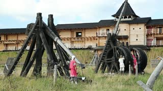 UKRAINE, KIEV REGION, KOPACHIV, AUGUST 14, 2016: People at cultural and entertainment festival in Kyivan Rus park in Kopachiv village, historical reconstruction of ancient Kiev, old wooden catapults