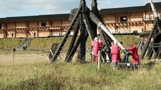 UKRAINE, KIEV REGION, KOPACHIV, AUGUST 14, 2016: People near old wooden catapults, cultural and entertainment festival in Kyivan Rus park in Kopachiv village, historical reconstruction of ancient Kiev