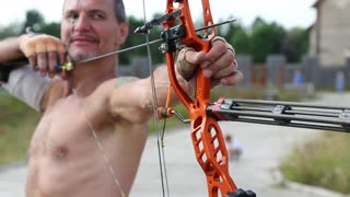 UKRAINE, KIEV REGION, KOPACHIV VILLAGE, AUGUST 14,2016: Archer shoots a bow at a target. Man training at archery with bow and arrow. Man holds bow in his left hand