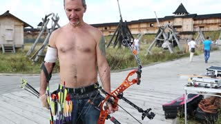 UKRAINE, KIEV REGION, KOPACHIV VILLAGE, AUGUST 14,2016: Archer shoots a bow. Man training at archery with bow and arrow. Archer shoots a bow at a target. Man holds bow in his left hand