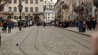 UKRAINE, LVIV, APRIL 5, 2015: White tram and people on the Market Square - is a central square of the city of Lviv in Western Ukraine