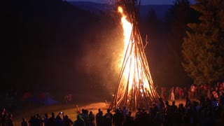 UKRAINE, PYLYPETS VILLAGE, JULY 6, 2015: People near the bonfire celebrate the feast of Ivan Kupala Day or Kupala Night - folk festival of the Eastern Slavs. This festival dedicated to the summer solstice