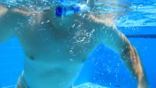 Underwater swimming. Man swims in the pool