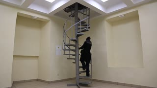 A woman rises up the spiral stairs