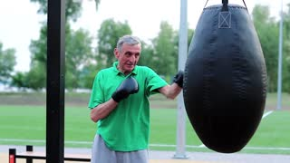Active elderly boxer in boxing glove training in a boxing club. Senior man boxing with a punching bag. Boxer hits punching bag. Aged grey-haired man in green t-shirt training in outdoor gym