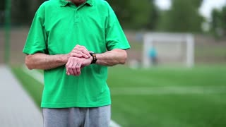 Active elderly man in green t-shirt runs around a football field. Senior man runs near football field. Man note down the time in his watch and start run. Physical activity helps to burn up calories