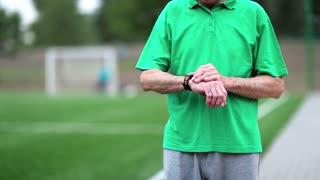 Active elderly man runs around a football field. Senior man runs near football field. Man note down the time in his watch and start run. Physical activity helps to burn up calories