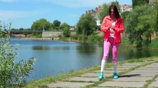 Active young woman running near lake. Girl goes in for sports,girl engaged in fitness. Girl in sports jacket note down the time in his watch and start running. Physical activity helps burn up calories
