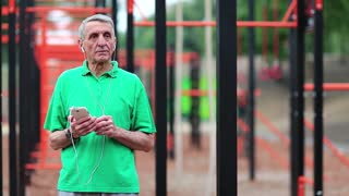 Aged sportsman listens to music on smartphone. Senior man with cell phone stands near sports ground. Active elderly athlete hold in hands mobile phone. Grey-haired man in the open air gym