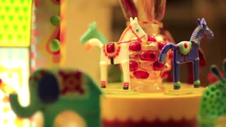 Animals in shop window in confectionery. Horses on the merry-go-round in candy store. Colorful caramel animals in sweets shop
