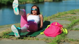 Athletic girl doing physical exercises and pumps press. Sportswoman lies on green mat near the lake and train abdominal muscles. Woman goes in for sports, physical activity helps to burn up calories