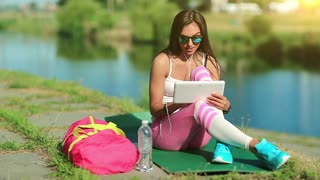 Attractive girl in sportswear with tablet computer communicates through skype