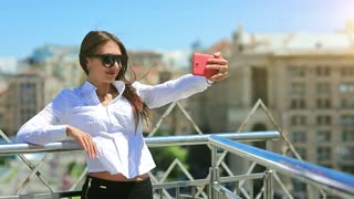 Attractive girl in sunglasses with red cell phone. Businesswoman makes selfie on his smartphone. Woman makes photos on mobile phone