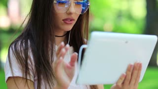 Attractive woman in big glasses uses tablet computer. Beautiful woman with white tablet pc in public garden. Female with tablet pc, she is in a merry mood