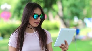 Beautiful girl communicates via tablet computer. Attractive woman with white tablet computer communicates through skype or video chat, female with tablet pc