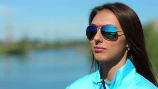 Beautiful woman in blue sports jacket drinks water. Attractive girl in sunglasses drinks clean mineral water from bottle