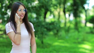 Beautiful woman in glasses talks on the mobile phone. Attractive woman stands in public garden and speaks on cell phone. Female with white smartphone