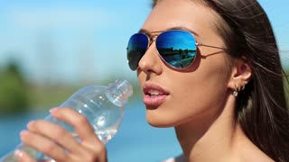 Beautiful woman in sunglasses drinks water. Attractive girl in glasses drinks clean water from bottle