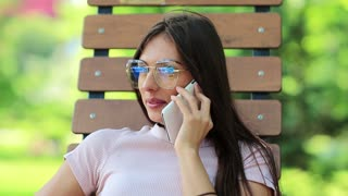 Beautiful woman sits on the bench and talks on mobile phone. Businesswoman with smartphone sits in public garden. Attractive girl speaks on cell phone, female with white smartphone