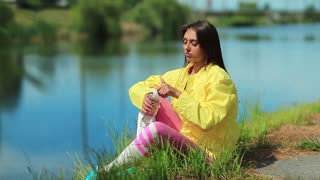 Beautiful woman sits on the grass near the lake and drinks water. Attractive girl in sportswear drinks clean water from a bottle. Girl opens bottle of water and drink, female drinks soda water