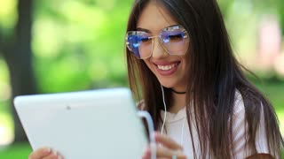 Beautiful woman uses tablet computer. Attractive woman in big glasses with white tablet pc in public garden. Female with tablet pc, she is in a merry mood