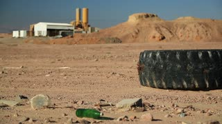 Big old tyre and rubbish lies in desert near Aqaba city in Jordan. Factory on the background. Abuse of environment. Black tyre and other garbage in desert, environmental pollution