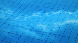 Blue clean water in swimming pool. Clouds are reflected in water