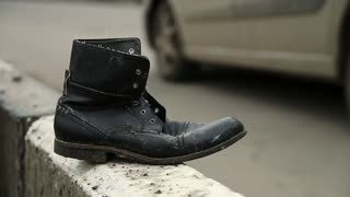 Boot near the highway, traffic violation and road accident. Old black shoe near the road. Jaywalking, do not run across road