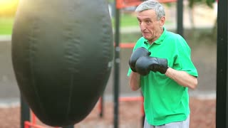 Boxer hits punching bag. Active elderly boxer in boxing glove training in a boxing club. Senior man boxing with a punching bag. Aged grey-haired man in green t-shirt training in outdoor gym
