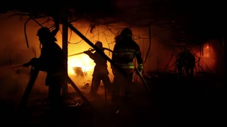 Brave firemen inside burning building. Fire extinguishing, fire brigade inside burning premises. House destroyed by fire