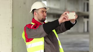 Builder at construction site records videos on smartphone. Worker in white hard hat with smartphone at project site