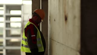 Builder knocks his head against the wall. Stressed worker in hard hat stands on construction site and knocks his head against the concrete wall, self-condemnation and self-reproach