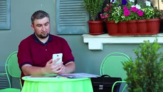 Businessman communicates via smartphone in summer cafe. Man sits at the table in summer restaurant and speaks on cell phone in video chat, tablet computer and business papers lies on the table